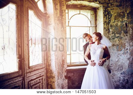 Newlyweds Hugging At The Door In An Old House.