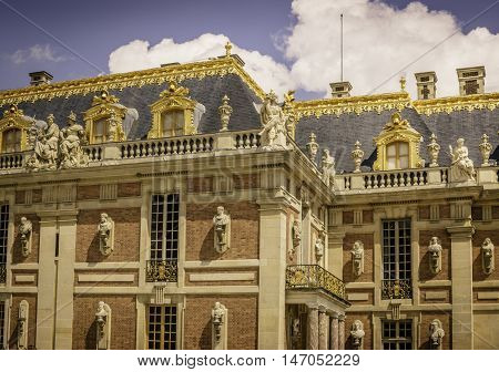 VERSAILLES, FRANCE - MAY 27, 2016: A small section of the majestic exterior of Versailles Palace, looking from the Marble Court. The Palace, built during the reign of King Louis XIV, was used as an occasional residence for the Royal Court. It is now a maj
