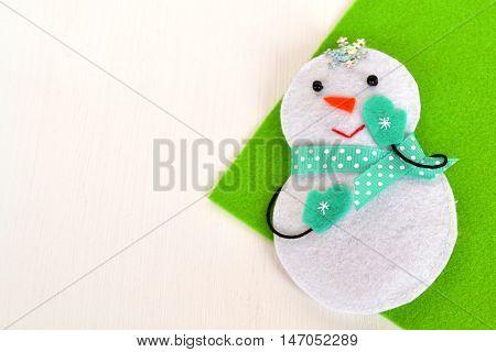 Christmas snowman ornament.  Snowman toy is sewn of felt. Christmas crafts idea. Christmas background