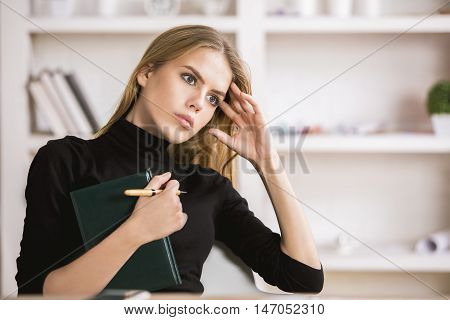 Girl With Notepad Thinking At Workplace