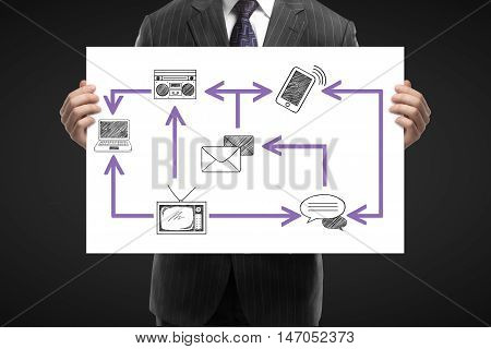 Closeup of businessman in suit holding whiteboard with abstract technology network on dark background. Communication concept