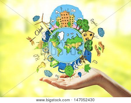 Female hands holding creative sketching of globe with natural healthy lifestyle icons on bright yellow background. Green world concept