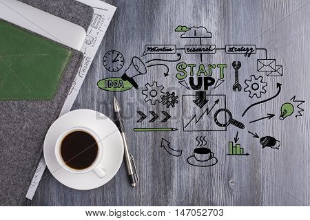Top view of wooden desktop with business sketch coffee cup pen and electronic device in cover. Start up concept