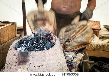 Traditional blacksmith uses bellows to keep a fire to melt metal