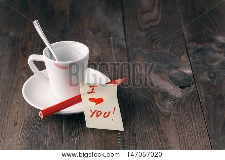 Cup Of Coffee With Lipstick Mark And Note 'i Love You' On Table Close Up