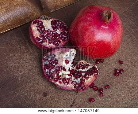 Red ripe open pomegranate on wooden background