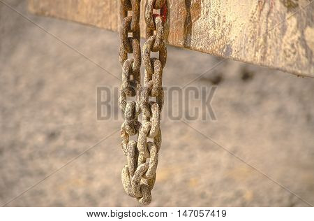 HDR old chain hangs on a excavator in a concrete plant