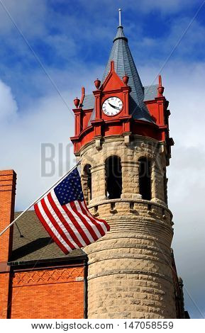 Opera house and city hall has unique Victorian architecture. Round tower houses dormers and clocks. Historic building can be found in Stoughton Wisconsin.
