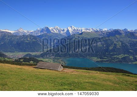Summer scene in the Swiss Alps. View from Mt Niederhorn. Famous mountains Eiger Monch and Jungfrau. Blue Lake Thunersee.