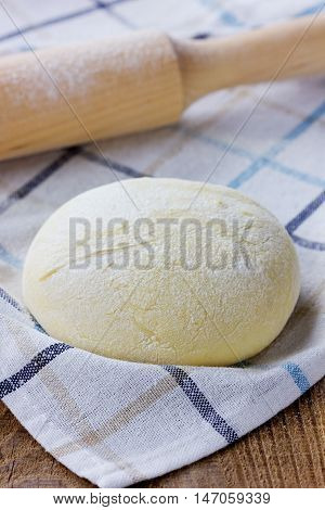 Pizza or bread dough with rolling pin on a linen napkin on the wooden table.