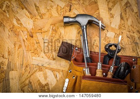 Hand Tools In Tool Belt On plate Of Pressed Wood Waste Close-up