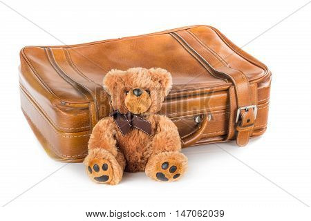 Teddy bear next to a leather suitcase