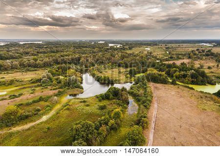 Autumn landscape with dramatic sky in the background in rich colors from above. Aerial view. Outdoor. Lush green field with river and backwater skyline.
