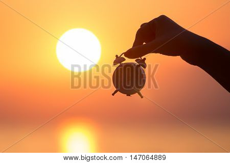 Silhouette of female hand holding small alarm clock and sunrise over sea in the background. Getting up early concept.