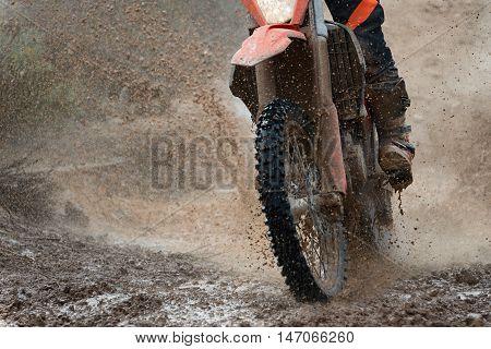 Motocross driver splashing mud on wet and muddy terrain