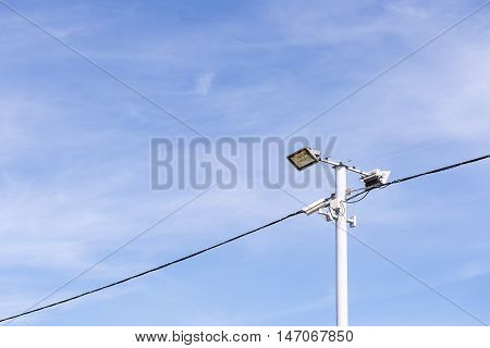 The street lamp and equipment electric post electric line with the blue sky.The spot lights at the car parking in daylight scene.