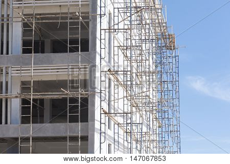 The building between the construction with the scaffolding with the sky.The building under construction with the scaffolind at the construction site.