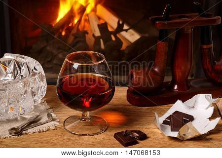 A glass of brandy chocolate and tobacco pipes on oak table on the background of a burning fireplace