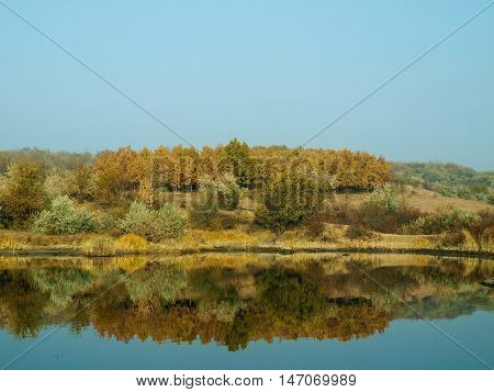 Beautiful autumn landscape on the bank reflected in the calm surface of the river serene day