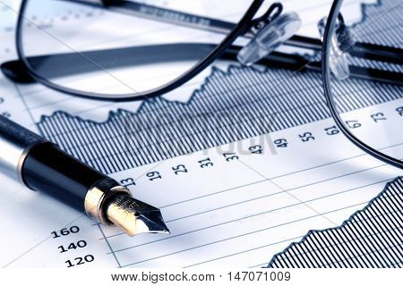 Glasses And Fountain Pen On Financial Graphs Close-up