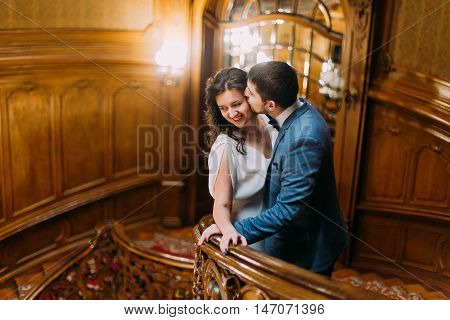 Charming newlywed pair embracing leaning on balustrade at gorgeous antique stairs with the background of royal wooden vintage interior.