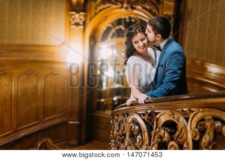 Charming newlywed pair embracing and kissing leaning on balustrade at gorgeous antique stairs with the background of royal wooden vintage interior.
