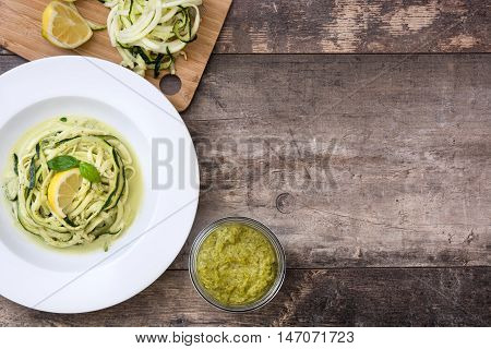 Zucchini noodles with pesto sauce on wooden background