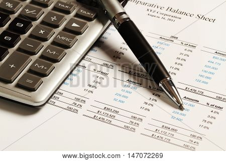 Pen And Calculator On Comparative Balance Sheet Close-up