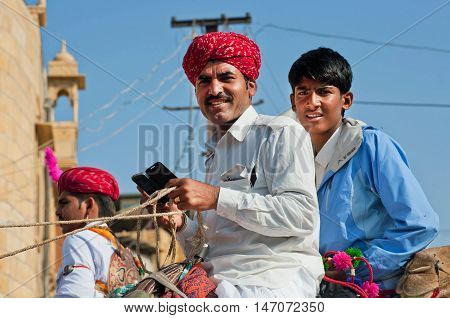 JAISALMER, INDIA - FEB 1, 2015: Two young drovers sitting on a camel with mobile phone in hands during the Desert Festival on February 1, 2015 in Rajasthan. Every winter Jaisalmer takes the Desert Festival