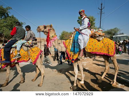 JAISALMER, INDIA - FEB 1, 2015: Camel rider in colorful dress goes past the tourist crowd of popular Desert Festival on February 1, 2015 in Rajasthan. Every winter Jaisalmer takes the Desert Festival