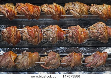 Rows of chickens cooking on a vertical rotisserie
