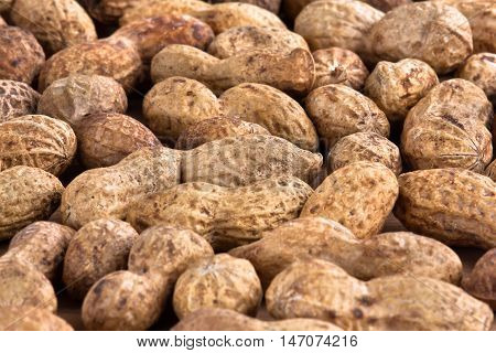 heap of unshelled peanuts as background closeup