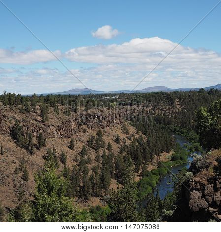The Deschutes River in Central Oregon is radiant b\ue as it cuts through a canyon.