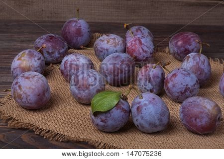 plums on the wooden background with sackcloth.