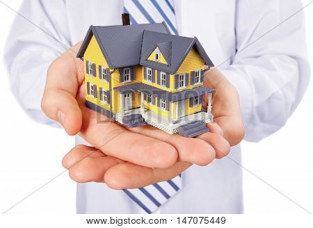 Men's Cupped Hands Holding a Model of a House - Isolated