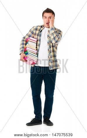 Full lenght portrait of shocked teenager with books. Male student expressing shocking emotions. Young man holding textbooks isolated on the white background.
