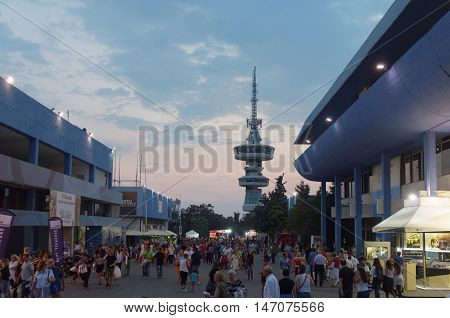 Thessaloniki, Greece - September 12 2016: 81st International fair night visitors. 81st Thessaloniki International Fair takes place from 10 to 18 September 2016. OTE telecommunications tower is visible.