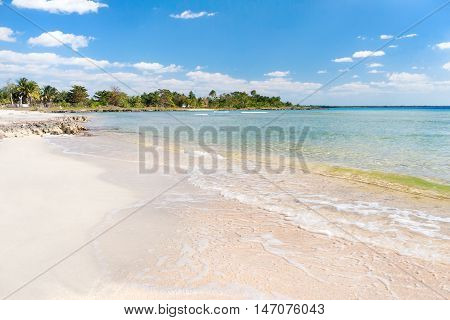 Soft wave of the sea on the sandy beach. Blue sky white sand palm trees and azure sea. Cuba Varadero Caribbean sea.