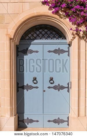 Old wooden door with stained glass old fashioned door knocker and bougainvillea flowers . Mdina Malta.