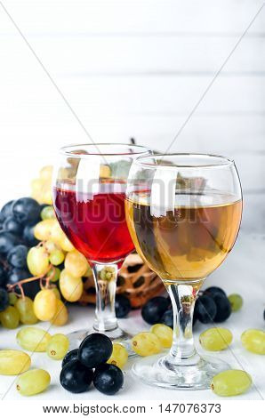 red and white wine in glasses with grapes on the white background