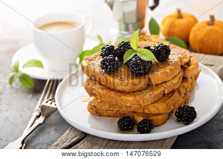 Pumpkin french toast with berries and maple syrup for breakfast