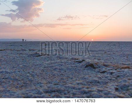 Sunrise in Sahara desert. Two man greeted dawn at salt lake. Egypt.
