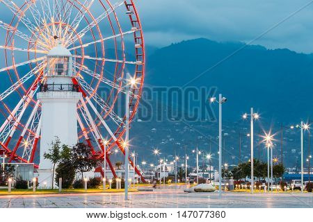 Batumi, Adjara, Georgia. Close View Of Ferris Wheel Exactly Behind The Old White Lighthouse At The Seafront In Miracle Park, Amusement City Park On Blue Evening Sky And Mountainous Hazy Waves Background.