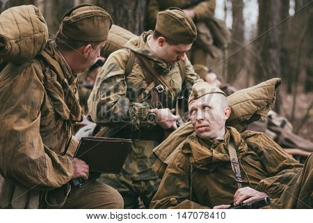 Pribor, Belarus - April 04, 2015: Group of unidentified re-enactors dressed as Soviet soldiers in overcoat resting in forest