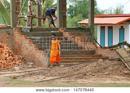 CHAMPASAK, LAOS - MAY 2015 : Young Buddhist novice holding a trowel at temple construction site in Champasak Province, southern Laos on May 24, 2015.