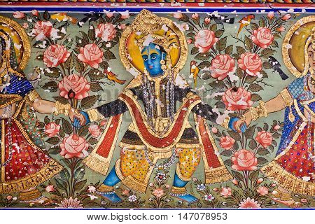 MANDAWA, INDIA - FEB 7, 2015: Lord Krishna dancing on a fresco with golden paint on carved wall on February 7, 2015. With population of 21000 Mandawa is a touristic site with its naive art Haveli houses