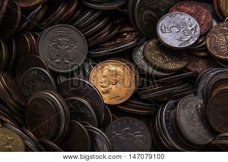 old russian coin from precious metal in a heap of modern coins of small face value