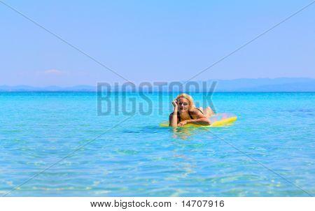 beautiful young woman in bikini on a matress in the sea