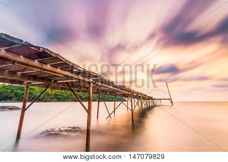 long explosure wood briged at small island pier and smoothe clouds