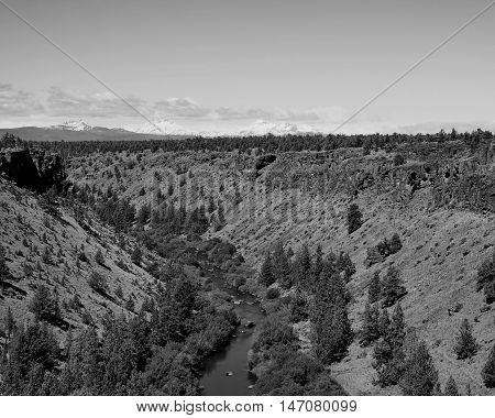 The Deschutes River in Central Oregon winds through the canyon it has etched over thousands of years while the Three Sisters of the Cascade Mountains look on.
